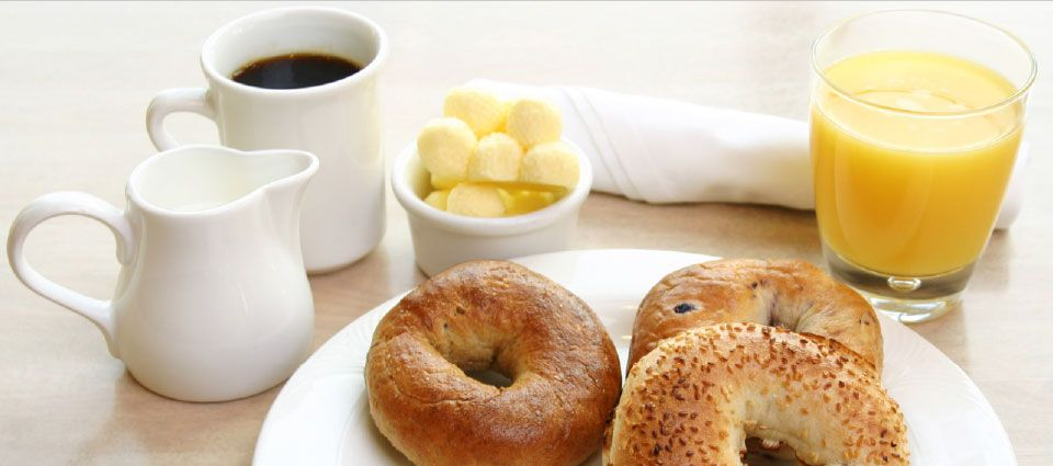 Coffee, milk, juice, bagel for breakfast